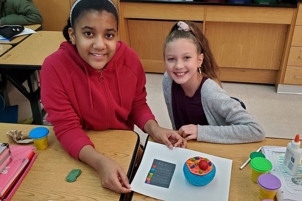 two girls with clay cell model on table