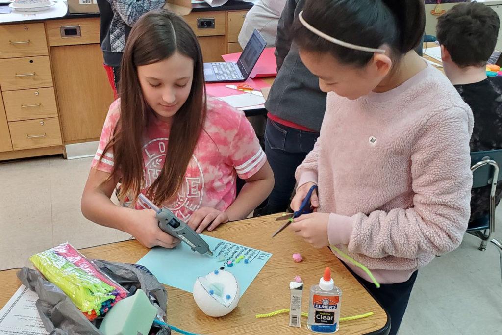 two girls making cell model using styrofoam ball