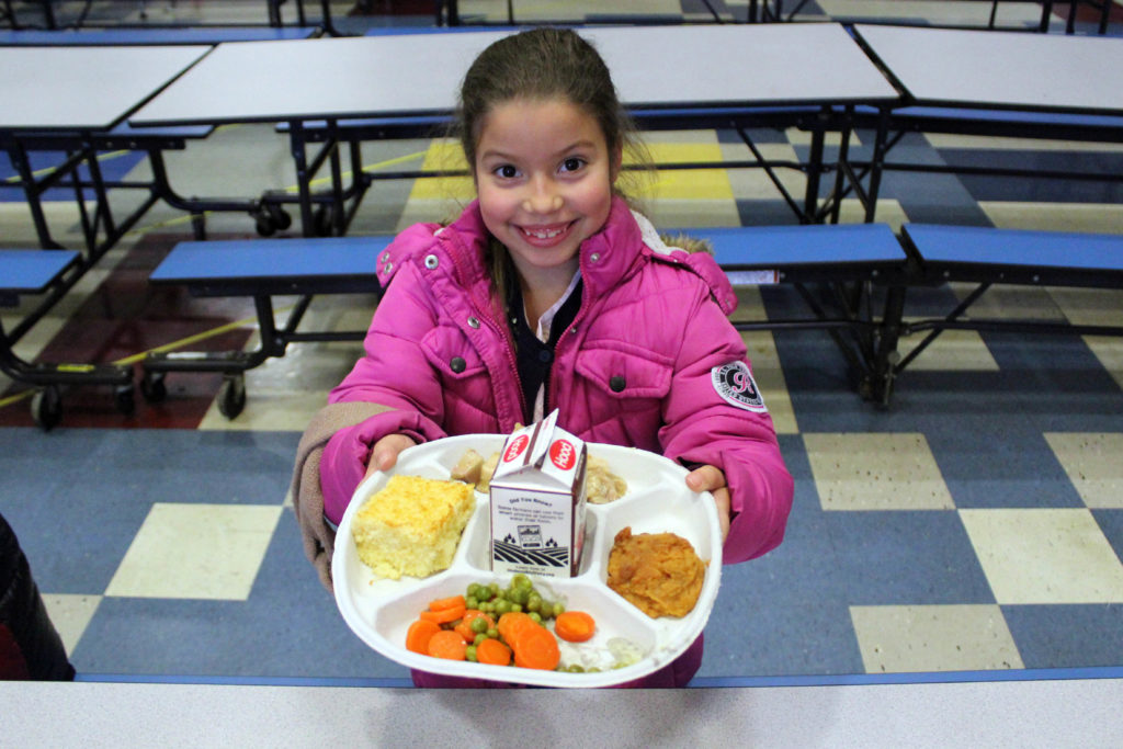girl holding up cafeteria tray full of food