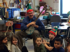 teacher wearing holiday hat and holding stringed instrument