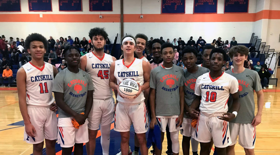 basketball team poses with player holding ball that says 1000 points
