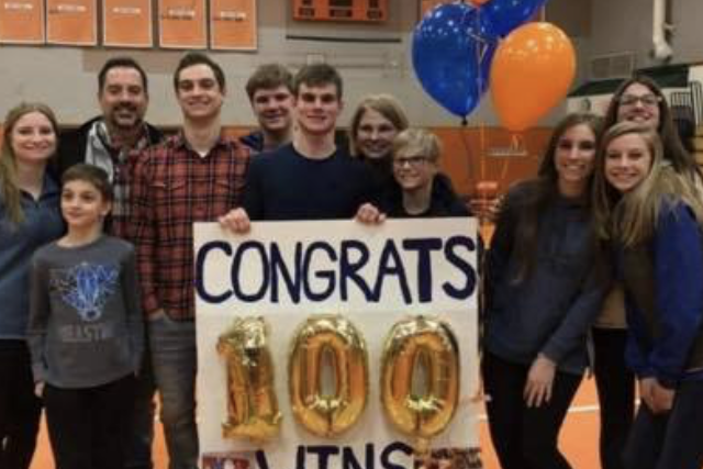 Jesse Davies and coaches holding up sign that says Congrats 100 wins Jesse!