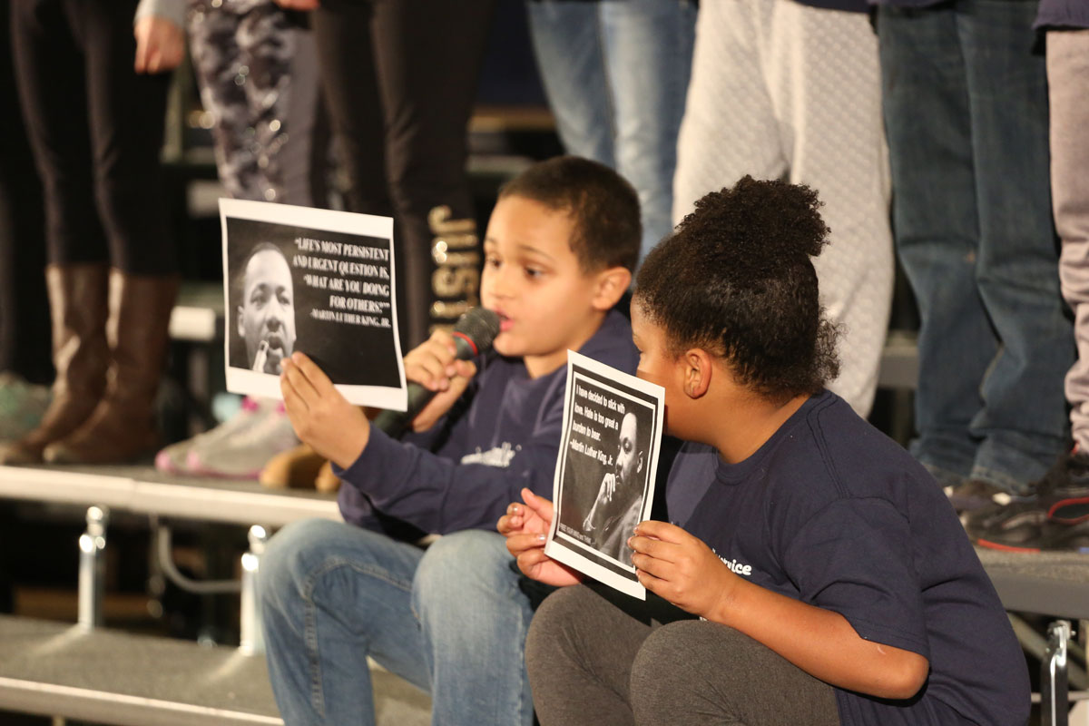 boy reads from flyer while girl looks on