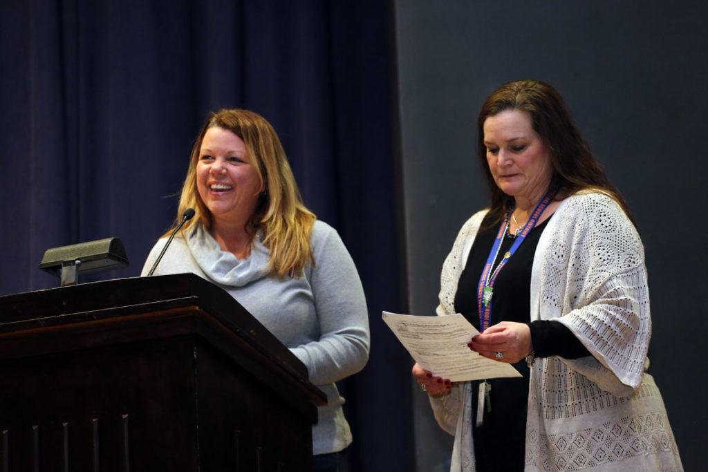 two women smiling at podium