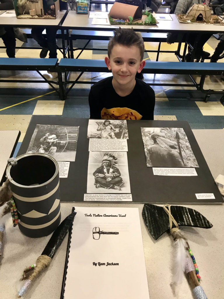 boy sitting behind photos of native Americans on table
