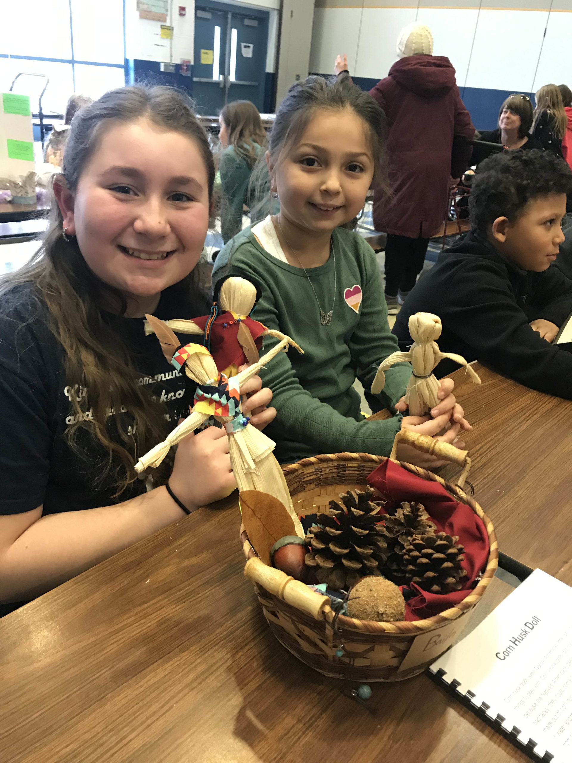 two girls playing with corn husk dolls