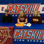 Katie Bulich sitting at table wearing Iona Soccer t-shirt and flanked by man and woman whee Iona College clothing