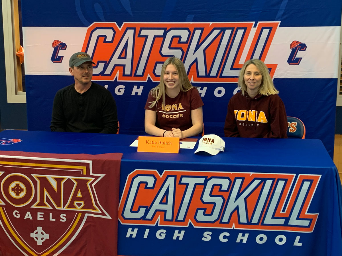 Katie Bulich sitting at table wearing Iona College t-shirt and flanked by man and woman whee Iona College clothing