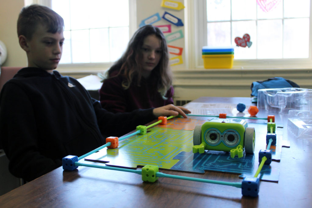 boy and girl watch robot move in pen