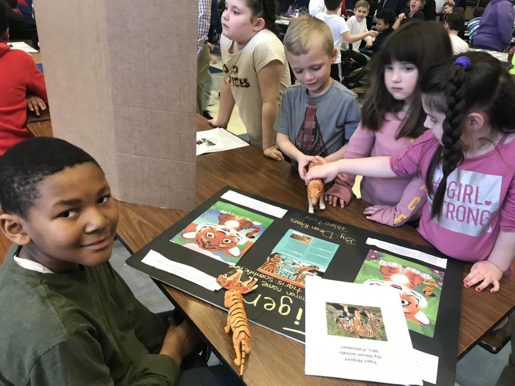boy and girls looking at animal display on table
