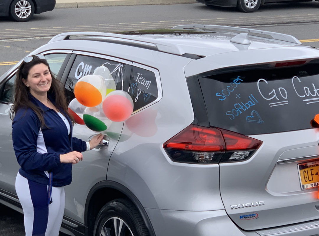 woman holding balloons next to decorated car