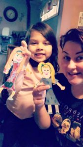 girl and woman holding paper dolls