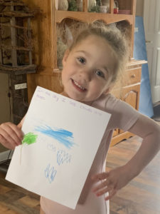 girl holding drawing of sky