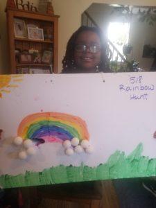 girl holding rainbow drawing