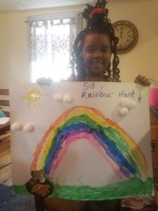 girl holding drawing of rainbow
