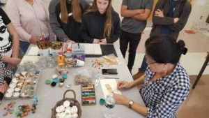 high school student and woman work on art project on classroom table