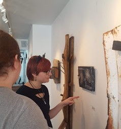 teenagers looking at artwork made from found scrapwood
