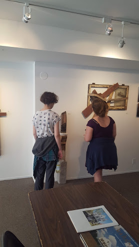 eenagers looking at artwork made from found scrapwood