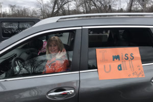 dog and woman in car with sign that says Miss U Guys