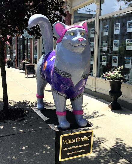Painted cat on post on street