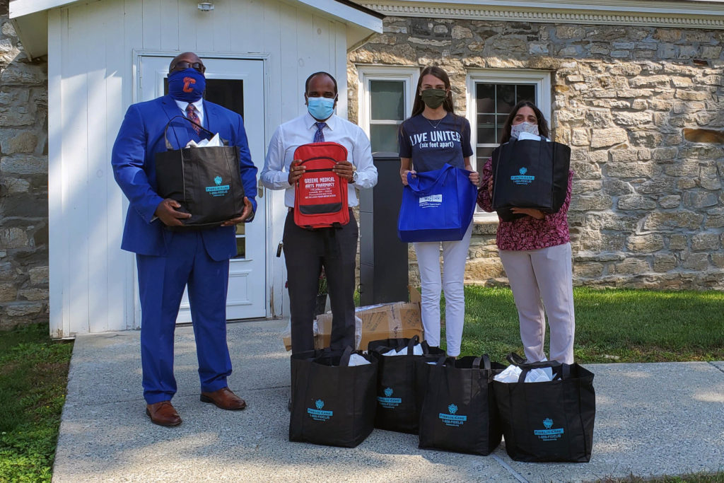 Two men and two women posing with bags of PPE