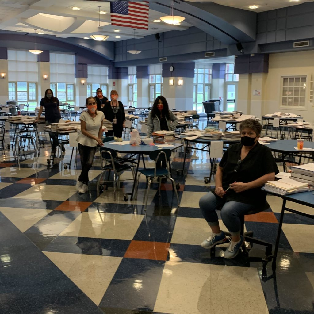 women wearing masks in cafeteria with tables of school supplies