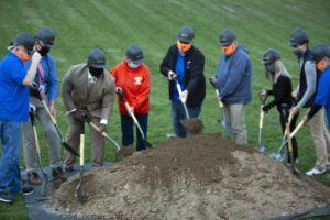 People wearing masks and hardhats shoveling dirt pile