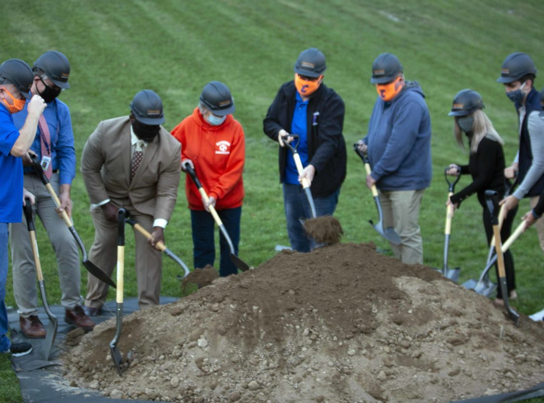 People wearing masks and hardhats shoveling dirt pile