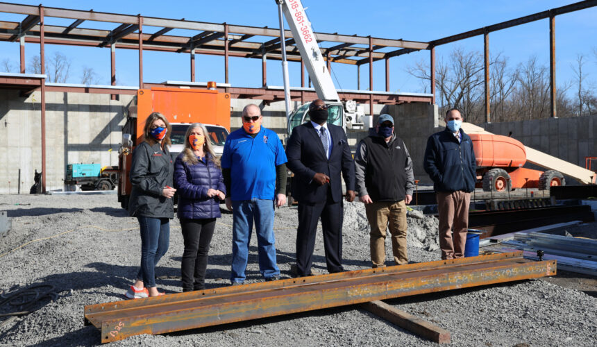 men and women standing behind steel i-beam