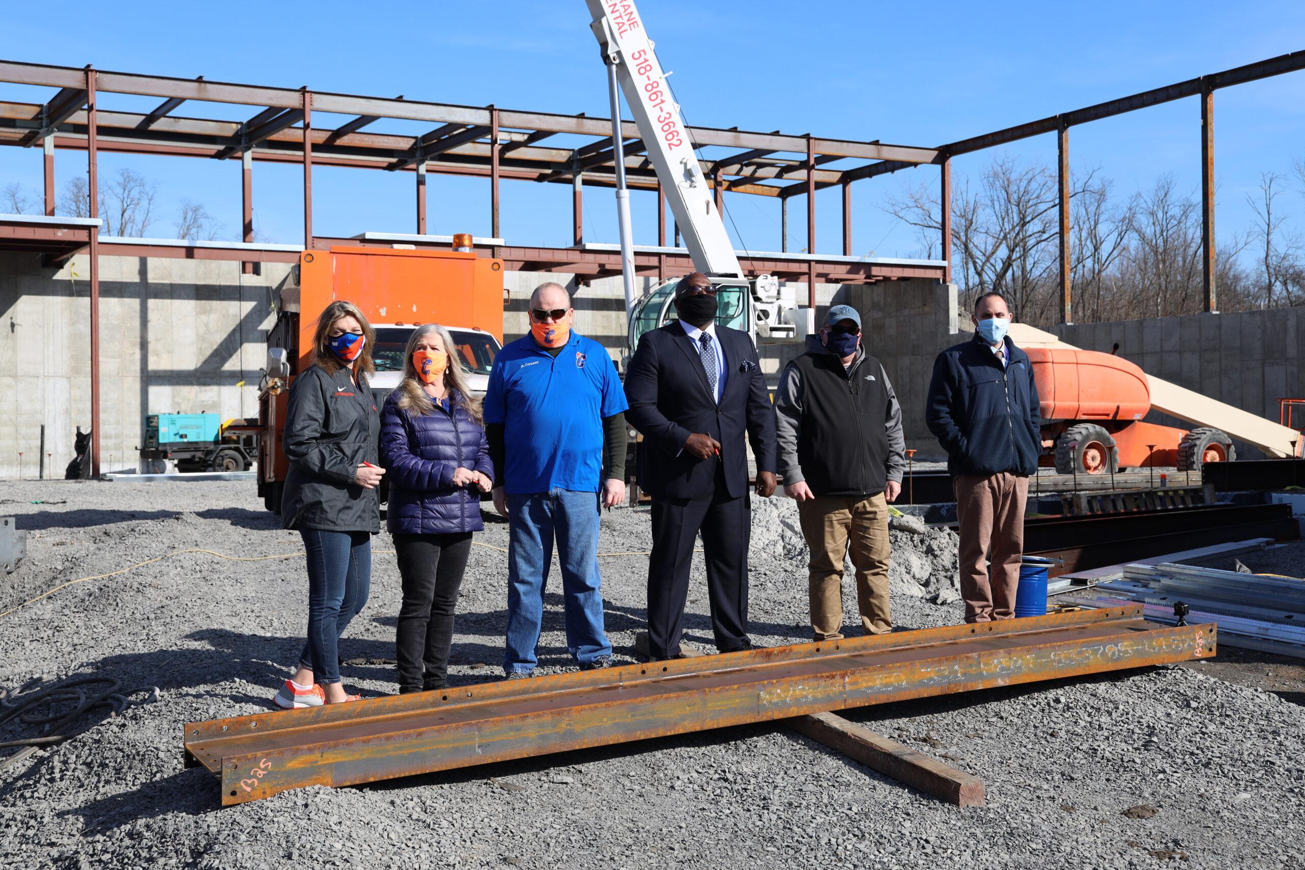 men and women standing behind steel i-beam