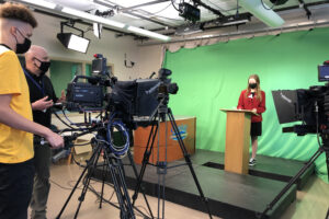 boy and man in school studio filming girl in red jacket