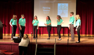 seven students wearing green shirts on stage