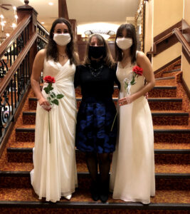 two girls in white dresses posing with woman in black dress