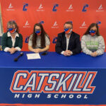 two girls, woman, and man sitting at table with Catskill High Banner on it, wearing masks