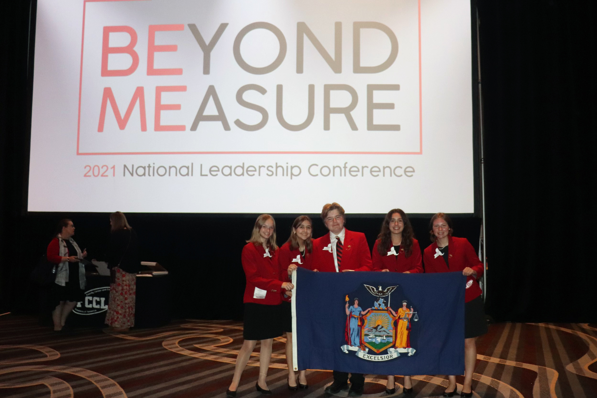 """Four girls an bou standing on stage in FCCLA uniforms in from of banner that reads """"Beyond Measure"""""""