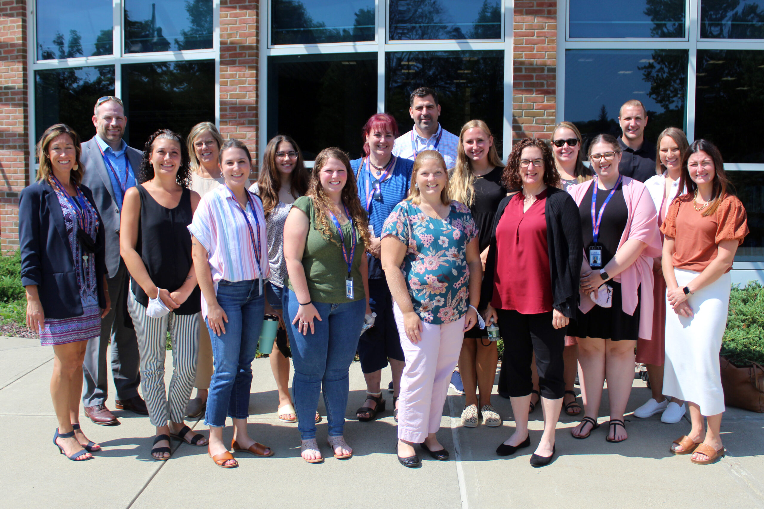 New faculty pose for photo outside CHS