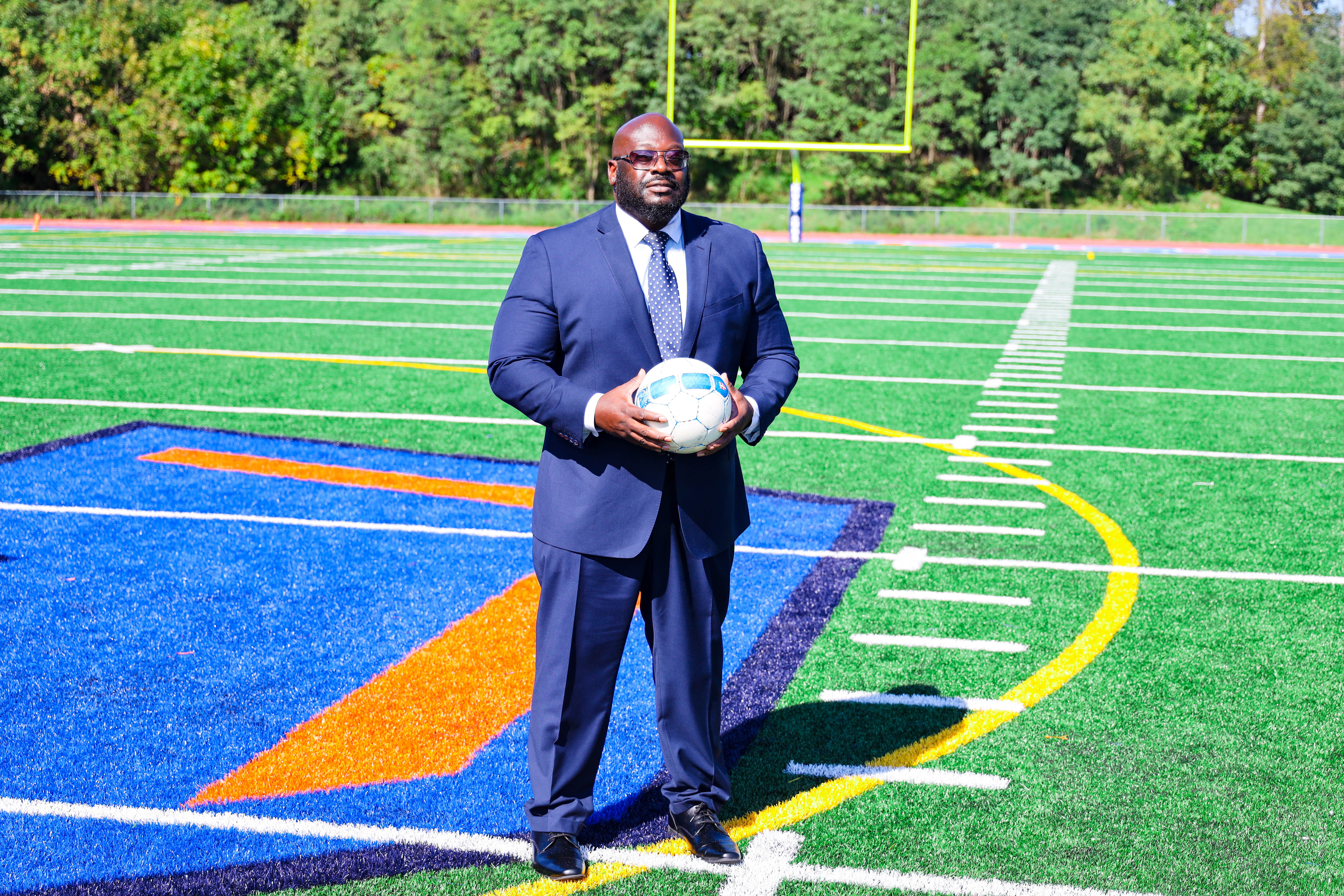 Dr. Cook holding soccer ball on turf field
