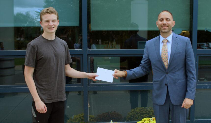 Mr. Shah handing letter to Nathan Riordon